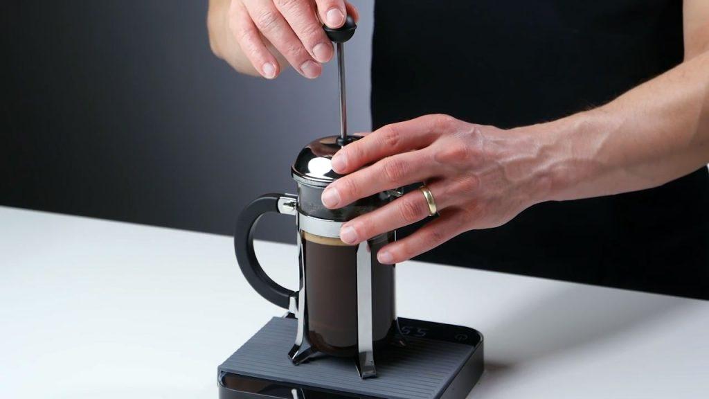 Presionando El Pistón De La Cafetera Francesa Para Filtrar El Café